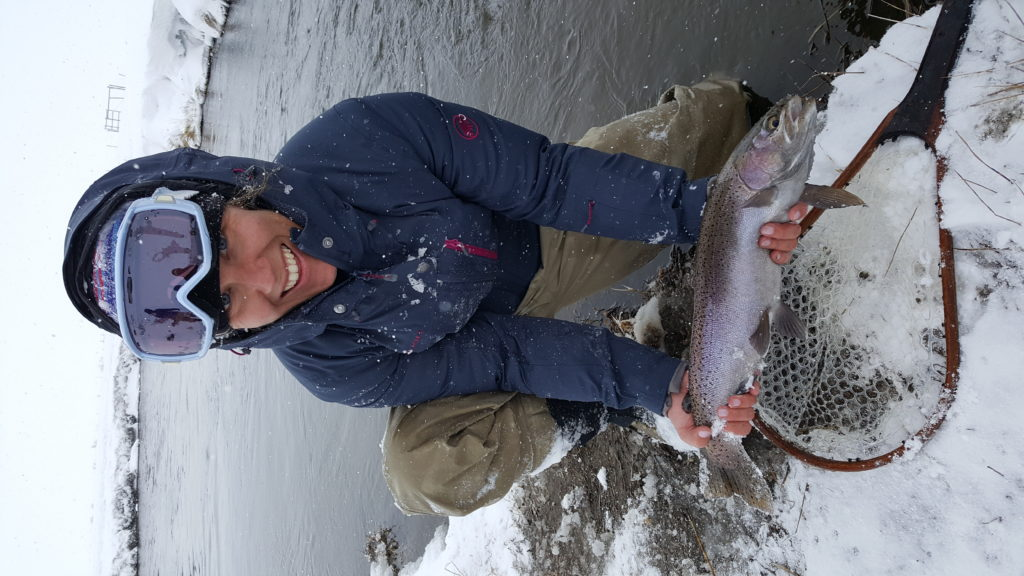 Large rainbow trout comes to hand a new Mammoth Lakes California while fishing in a blizzard