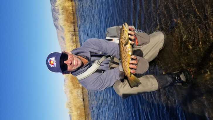 Fisherman with a hat holds up a large brown trout out of the over Owens River with grass on the sides and a large field