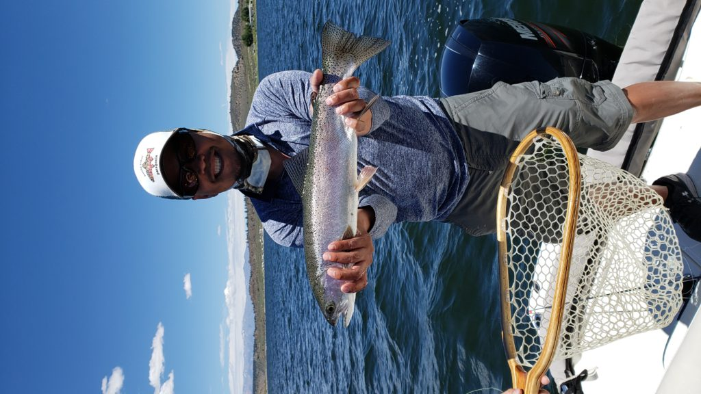 Big rainbow trout raised above the water on Crowley Lake standing over a boat.