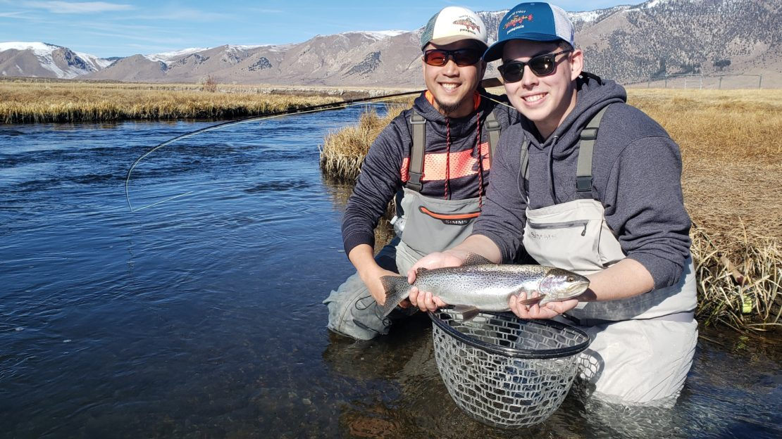 Father and Son pose with a trout over the Upper Owens River near Mammoth Lakes California