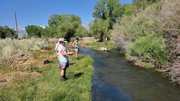 Three people Enjoying the Creek fishing of bishop california